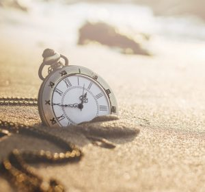 Vintage pocket watch on golden sand beach during sunrise or sunset in summer, Time concept